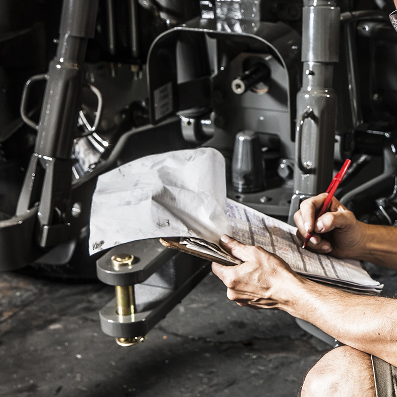 Man working on tractor suspension
